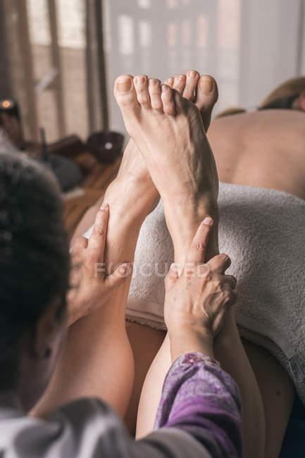 Terapeuta haciendo masaje de reflexología podal en paciente femenino - foto de stock