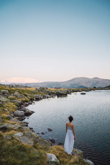 Young woman standing alone on shore of mountain lake — Stock Photo