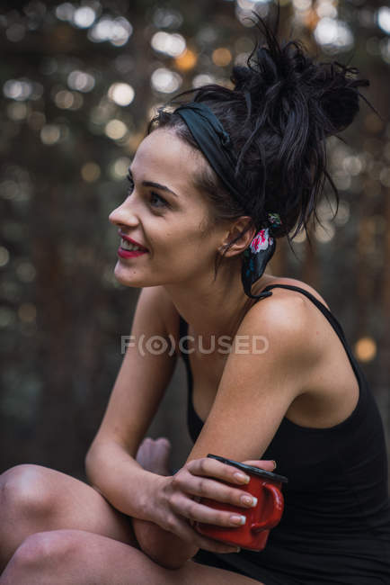 Charming brunette woman holding cup in nature — Stock Photo
