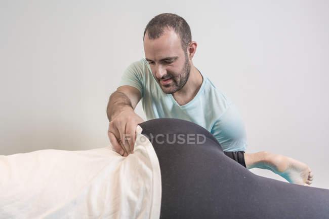 Terapeuta haciendo terapia alternativa tratamiento corporal para estimular los tejidos corporales en la sala de masajes - foto de stock