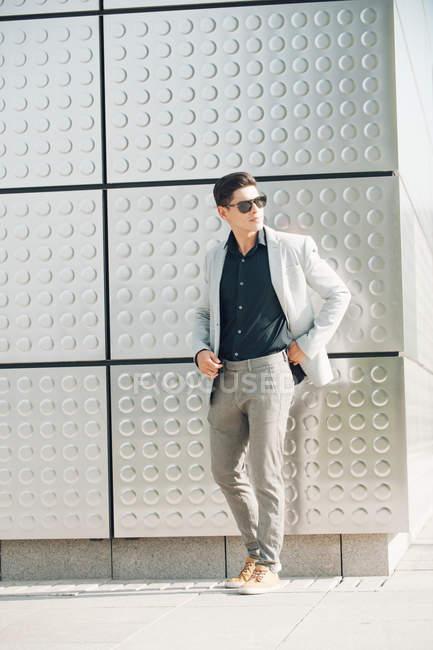 Chico joven en traje elegante de pie cerca de la pared del edificio - foto de stock
