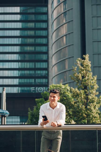 Молодой улыбающийся бизнесмен со смартфоном, опирающийся на перила перед современным зданием — стоковое фото