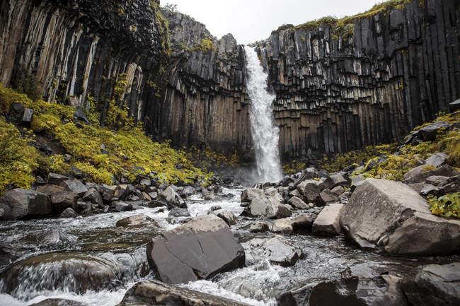 Pittoresca cascata che spruzza dalla scogliera rocciosa, Islanda — Foto stock
