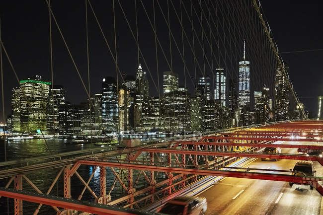 Vehicles riding on modern bridge over river in New York city at night, USA — Stock Photo