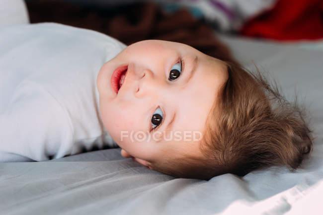 Смешной мальчик лежит на кровати и смотрит в камеру. — стоковое фото
