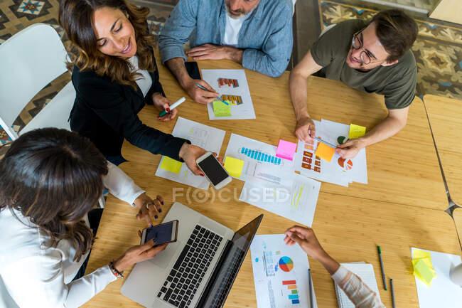 Вигляд з боку бізнесменів, які розглядають документи на зібранні за допомогою ноутбуків і смартфонів. — стокове фото