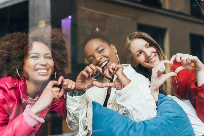 Группа из трех красивых молодых многорасовых женщин, сидящих в кофейне и смотрящих в окно — стоковое фото
