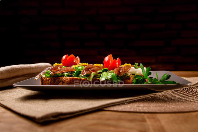 Sandwich with vegetables and fish on grey plate on wooden table — Stock Photo