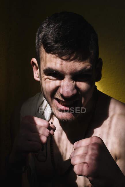 Fiducioso combattente sportivo senza maglietta in piedi con i pugni alzati e guardando la fotocamera. — Foto stock