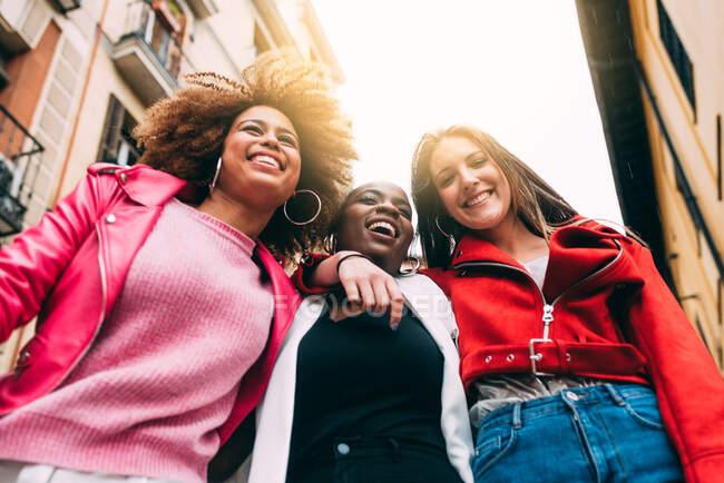 Група з трьох прекрасних молодих мультирасових жінок весело гуляють по вулиці. — стокове фото