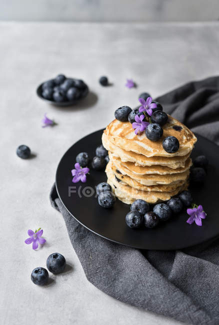 Stack of appetizing tasty crumpets with blueberries and purple flowers on black plate on grey background — Stock Photo