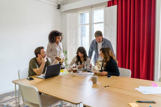 Колеги обговорюють графіки в офісі — стокове фото