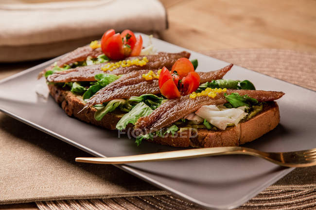 Sandwich with vegetables and fish on grey plate with fork — Stock Photo