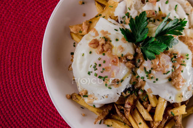 Appetizing portion of poached eggs served in plate with French fries — Stock Photo