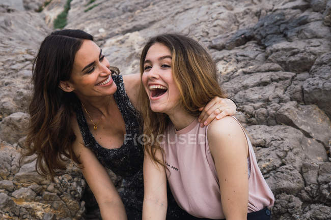 Two young female friends laughing in front of big rock — Stock Photo