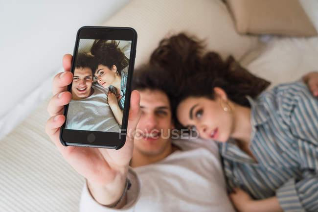 Prise de couple jeune gai selfie smartphone sur lit — Photo de stock