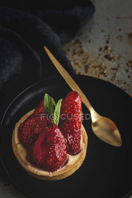 Delicious dessert filled with cream and fresh strawberries on black plate — Stock Photo
