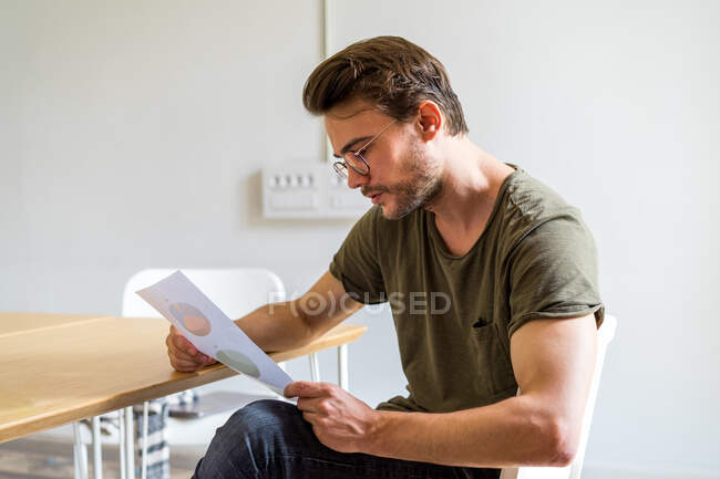 Side view of male in glasses sitting in office holding document and attentively considering it — Stock Photo
