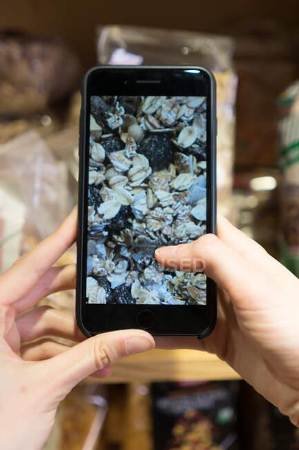 Recorte vista de cerca de la persona que fotografía muesli en el teléfono inteligente - foto de stock