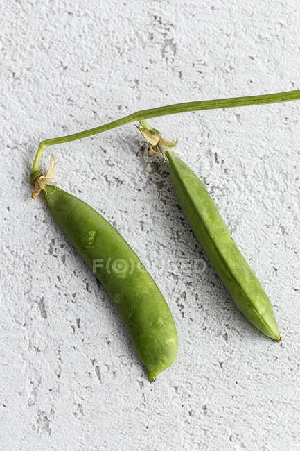 Close-up of green peas on white shabby surface — Stock Photo