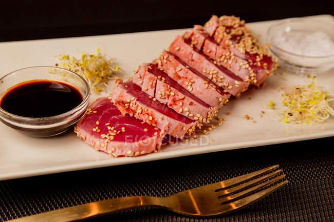 Filete de atún en rodajas crudas en bandeja con salsa sobre fondo negro - foto de stock