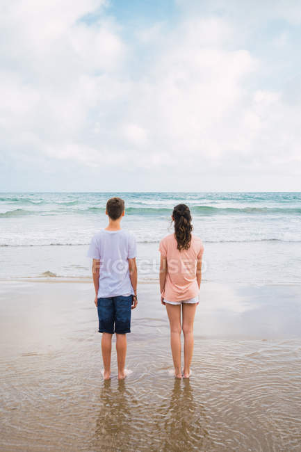 Teenager friends standing on beach and looking at view — Stock Photo