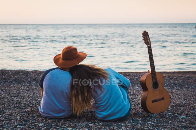 Пара з гітарою на пляжі. — стокове фото