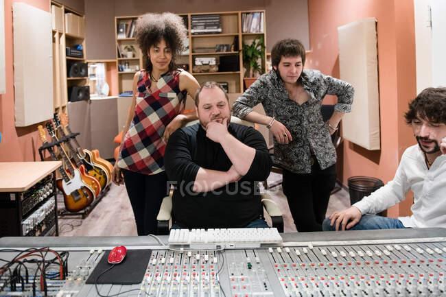 Diretores de som sentado na placa de mixer de áudio enquanto trabalhava em estúdio de gravação moderna — Fotografia de Stock