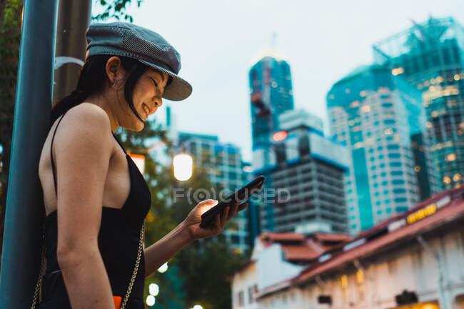 Seitenansicht einer Asiatin in stylischer Kleidung, die auf der Straße steht und ihr Smartphone benutzt. — Stockfoto