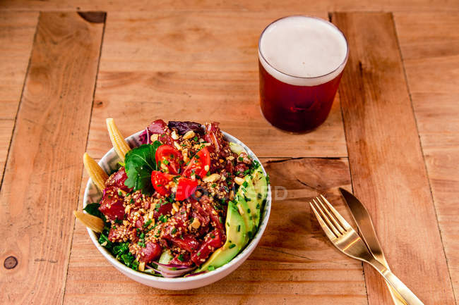 Bowl of tasty vegetable salad with avocado on wooden table with glass of beer — Stock Photo
