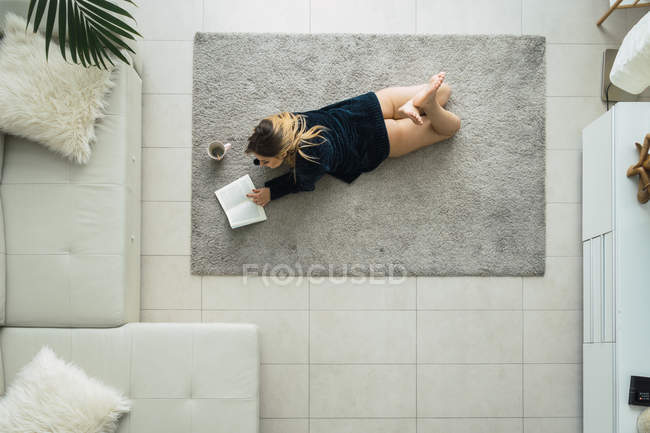 Young woman cuddling on carpet in living room reading book and drinking coffee — Stock Photo