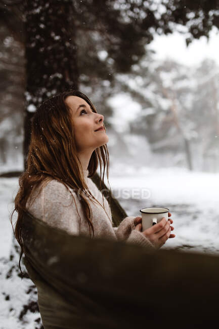 Side view of pretty dreamy young woman sitting in hammock and having hot drink in winter nature. — Stock Photo