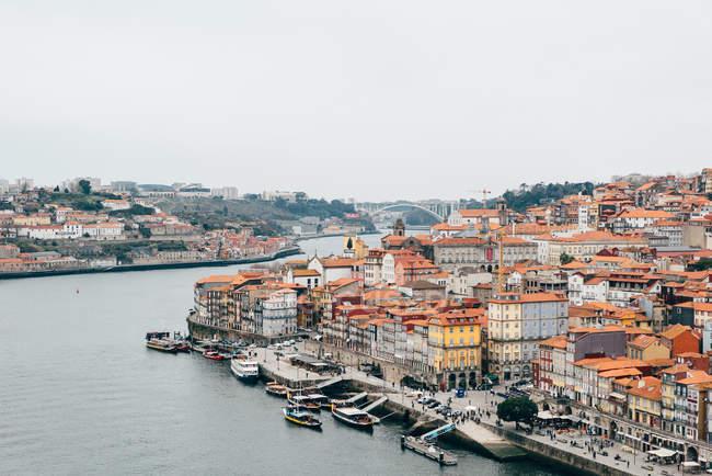Canale e città vecchia con tetti arancioni in nuvoloso, Oporto, Portogallo — Foto stock