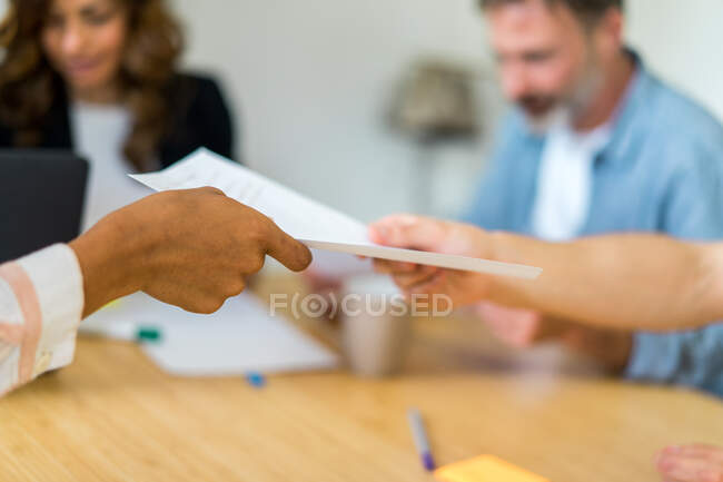 Businesspeople at meeting desk and considering documents — Stock Photo