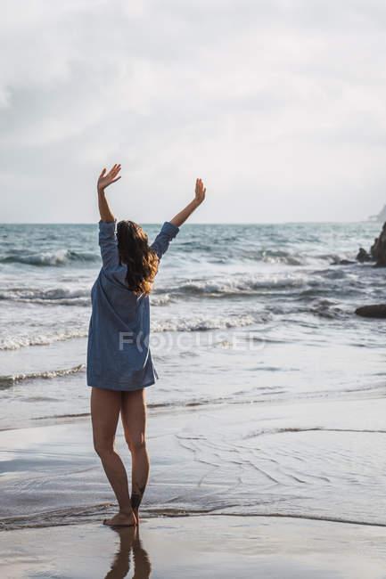 Donna con lunghi capelli castani in piedi sulla spiaggia con le braccia alzate — Foto stock