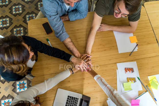 Crop view from above of office managers sitting at table and joining hands during a meeting — Stock Photo