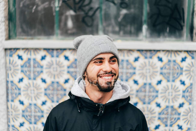 Ritratto di Allegro eccitato turista maschio in piedi al muro con piastrelle blu — Foto stock