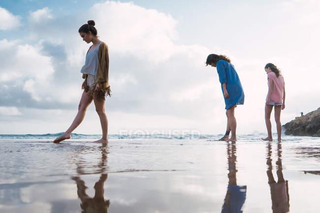 Женщина и девочки-подростки, идущие вместе по пляжу — стоковое фото