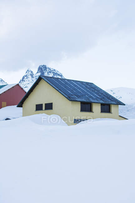View to small colorful houses and white snowy peaks in daylight. — Stock Photo