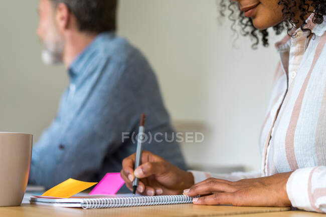 Worker sitting with colleague in office and writing in notebook — Stock Photo