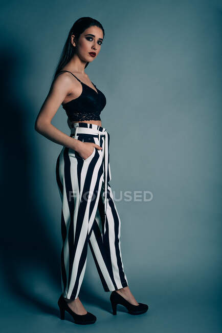 Side view of beautiful brunette female in bra and striped trousers putting hands in pockets looking at camera on gray background — Stock Photo