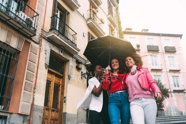 Group of three beautiful young multiracial women having fun walking on the rain — Stock Photo