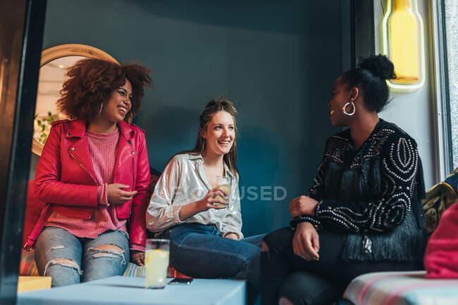 Gruppe von drei schönen jungen multirassischen Frauen, die in einem Café sitzen und interagieren — Stockfoto
