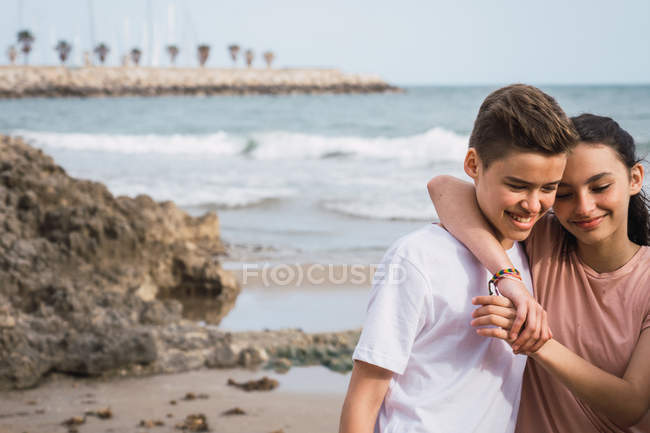 Smiling teen girl and boy standing on beach — Stock Photo