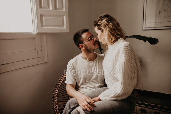 Happy couple sitting in armchair and looking at each other while bonding at home — Stock Photo