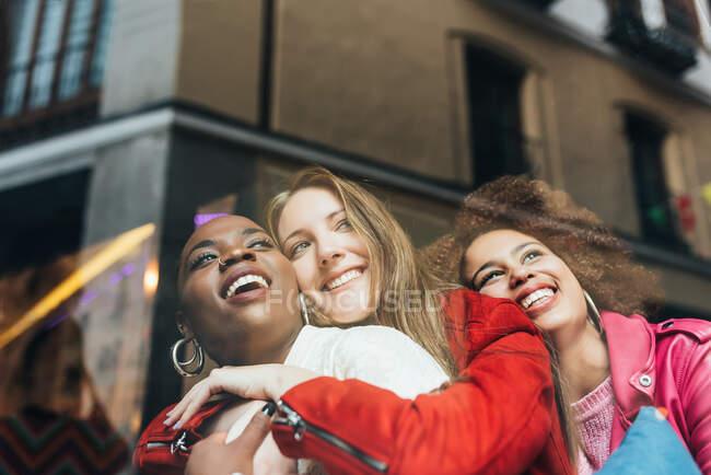 Gruppe von drei schönen jungen multirassischen Frauen, die in einem Café sitzen und zum Fenster schauen und einander umarmen — Stockfoto