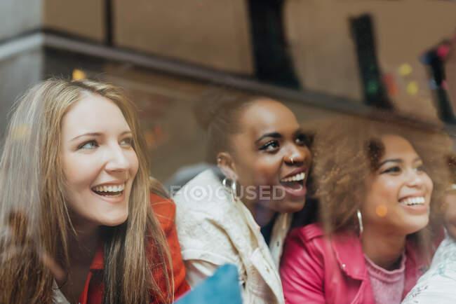Gruppe von drei schönen jungen multirassischen Frauen, die in einem Café sitzen und zum Fenster schauen — Stockfoto