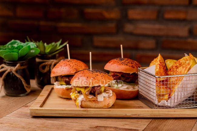 Tasty burgers and french fries in served on wooden tray — Stock Photo