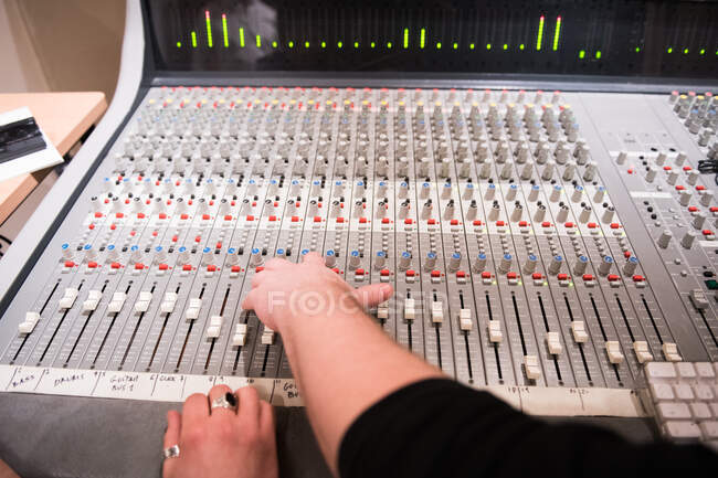 Crop hands pulling switches on audio mixer board in recording studio. — Stock Photo