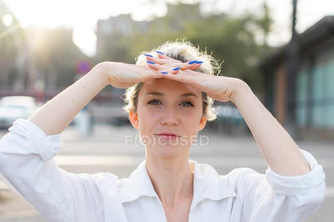 Портрет блондинки, смотрящей в камеру с руками над головой — стоковое фото